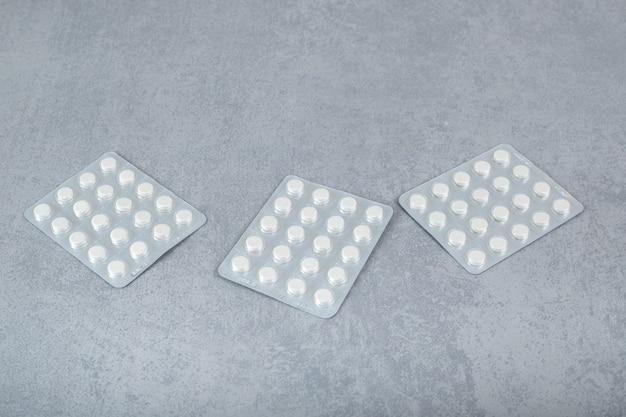 회색 표면에 흰색 알약이 있는 많은 물집