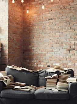 소파에 누워있는 많은 책. 아무도