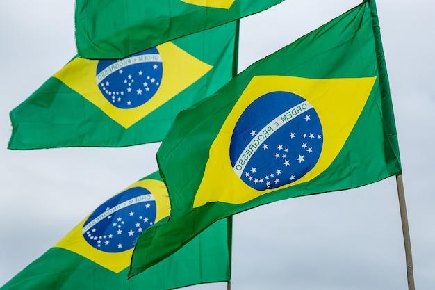 Много бразильских флагов на фоне облачного неба.