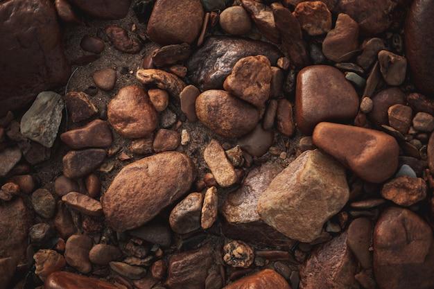 Много коричневых круглых булыжников, встроенных в пол, разных форм и размеров. зенит вид