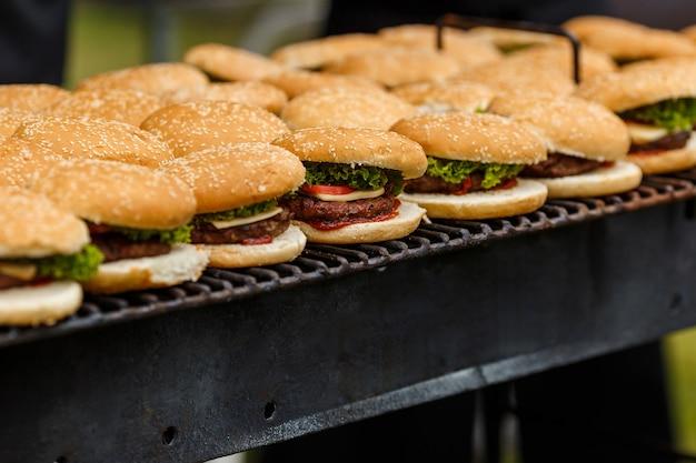 На гриле валяется много котлет. кейтеринг приготовление еды для вечеринки на природе барбекю на компанию