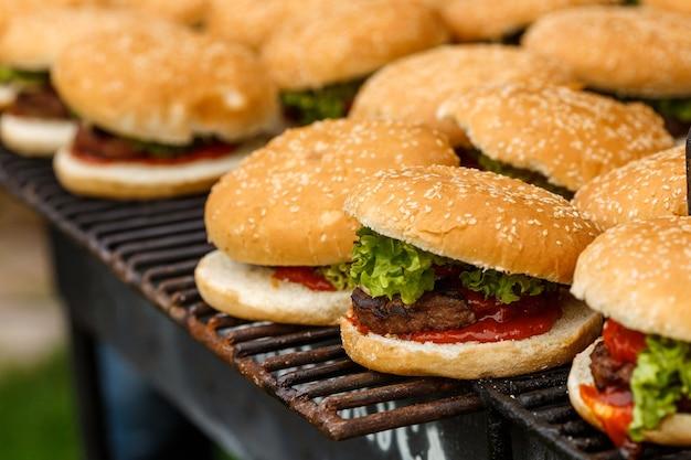 На гриле валяется много котлет. кейтеринг приготовление еды для вечеринки на природе барбекю на компанию Premium Фотографии