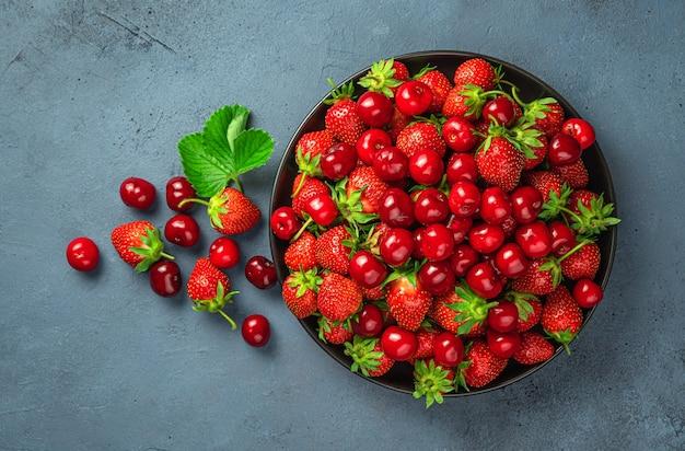 회색 파란색 배경에 접시에 많은 체리와 딸기. 건강한 딸기와 과일.