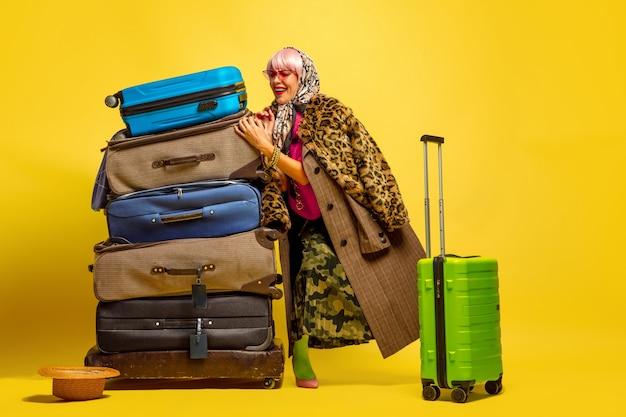 旅行に行く服がたくさん。黄色の背景に白人女性の肖像画。美しい金髪モデル。