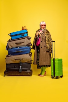 Много одежды для путешествий. портрет кавказской женщины на желтом фоне.
