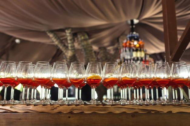 結婚式のパーティーでバーでカクテルをたくさん。 apperolとレモンのスライスとメガネをクローズアップ