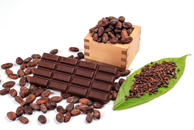 Много какао-бобов в деревянной коробке и куча какао-порошка на зеленом листе с плиткой шоколада, изолированной на белом фоне