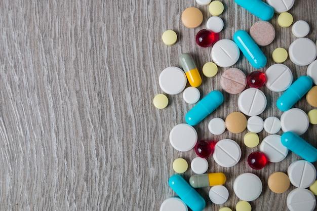 Много красочных лекарств и таблетки сверху на сером фоне деревянных. копировать пространство вид сверху, рама. обезболивающие, таблетки, дженерики, наркотики.
