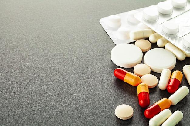 テーブルの上に横たわっているたくさんのカラフルな薬や錠剤