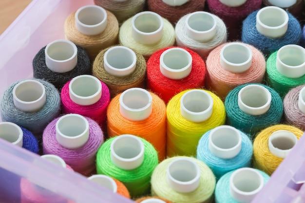 Много разноцветных швейных ниток в коробке селективный фокус крупным планом