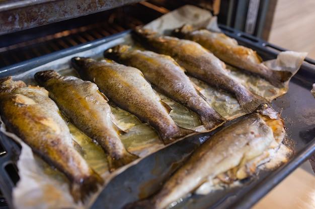 金属製のトレイの写真には、グリルやオーブンで焼いた焼き肉や魚の炒め物がたくさんあります...