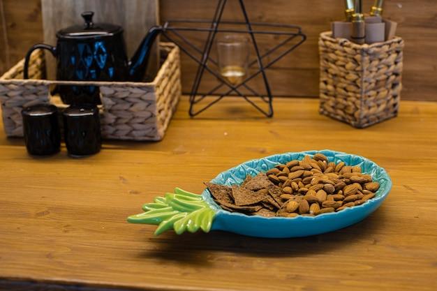 Много печенья в тарелке и разные кухонные принадлежности на коричневом столе