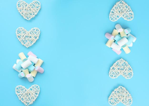 Много вкусных бело-желтых синих и розовых зефиров с белыми сердечками из ротанга на синем фоне