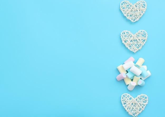 Множество вкусных белых, желтых, голубых и розовых зефиров с сердечками из белого ротанга.