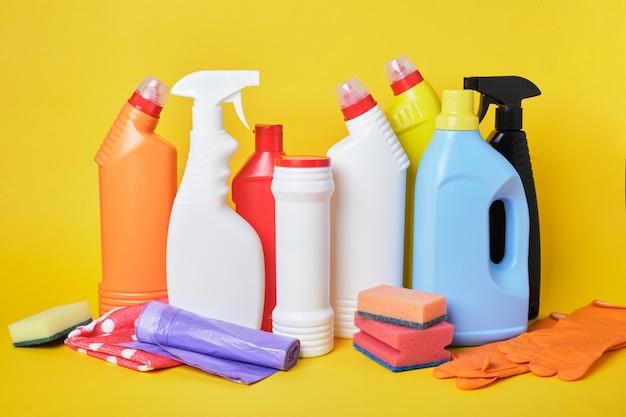Много бутылок с моющим средством и чистящих средств на желтом фоне