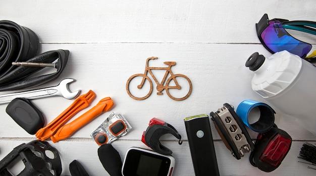 Множество различных велосипедных аксессуаров, лежащих на деревянном столе вокруг маленькой велосипедной иконы