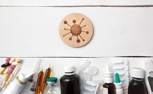 Множество разных лекарств, таблеток и других лекарств на деревянном белом столе и символы вируса между ними