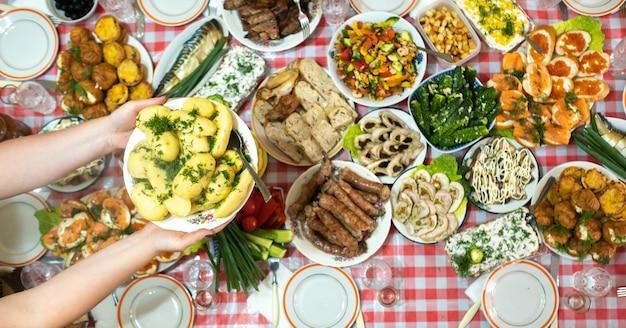 На банкетном столе много разной еды и подается отварной картофель с укропом.