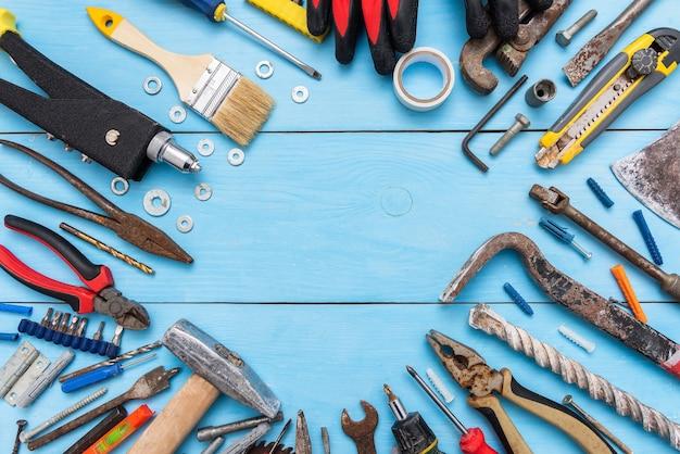 На столе много разных старых ржавых инструментов.
