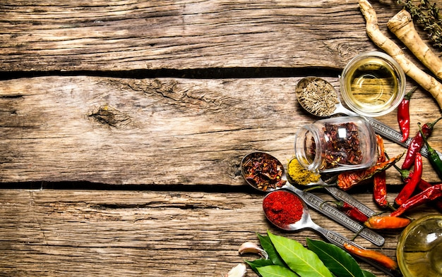 木製のテーブルにハーブとニンニクを入れたスプーンのさまざまなスパイスがたくさん。上面図