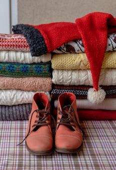 古い赤い靴でテーブルの上の2つの山に折りたたまれた多くの異なるセーターとプルオーバー