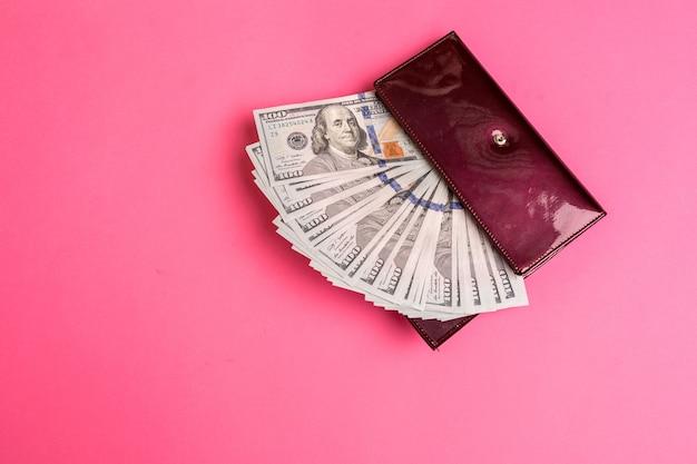 ピンクの背景に赤い女性の財布にたくさんのドル紙幣