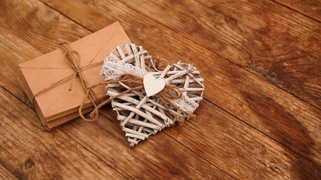 木製の手作りの白いハートと紐で結ばれたクラフト紙からの封筒がたくさん