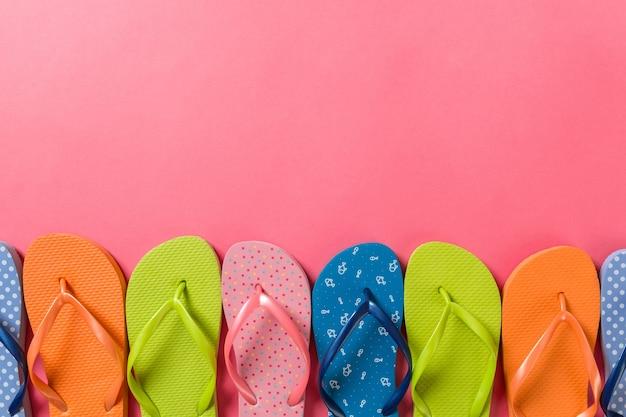 たくさんのフリップフロップ色のサンダル、色付きの背景の夏休み、コピースペースの上面図。