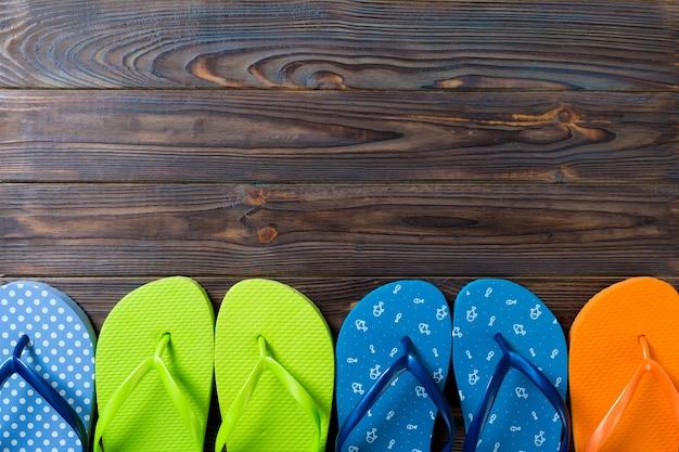 たくさんのフリップフロップ色のサンダル、木製の背景の夏休み、コピースペースの上面図。