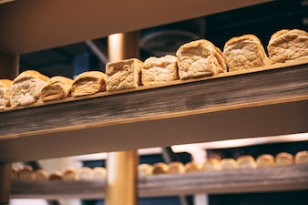 A lot of fresh baked loaf bread on wooden display.