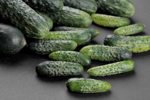 Много свежих огурцов разных сортов крупным планом на черном фоне. овощи