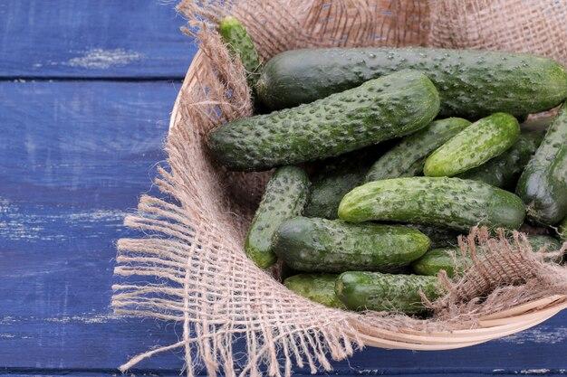 Много свежих огурцов разных сортов на синем деревянном фоне. овощи...