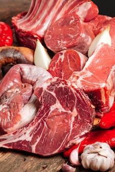 Много свежего сочного ферментированного мяса. сырые говяжьи стейки на деревянном столе