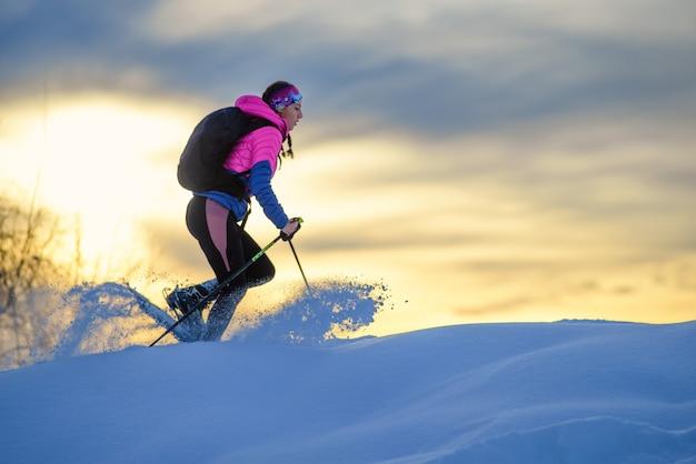 Много свежего снега, который движется там, где проходит девушка в снегоступах