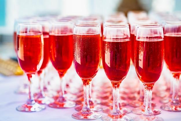 結婚式前のビュッフェテーブルでのゲストのためのロゼワインとグラスがたくさん