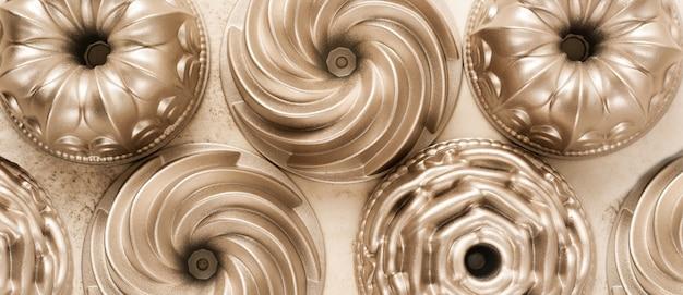 Множество золотых металлических форм для выпечки кексов на светло-коричневом бетоне.