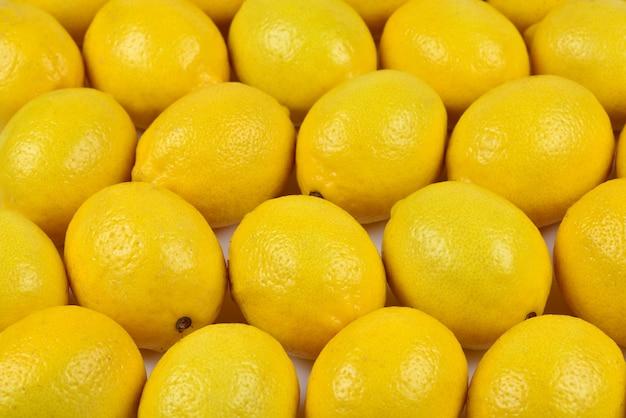 В коробке много сочных разноцветных лимонов. фон лимоны.