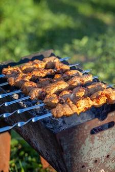 Много сочных мясных шашлыков подряд на мангале. кусочки мяса, нанизанные на металлические шпажки на решетке, на закате. процесс приготовления шашлыка с большим количеством дыма. готовим на природе
