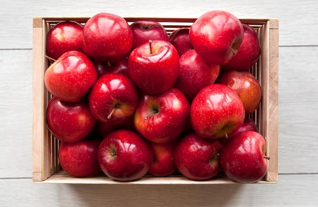 台所の木製のテーブルの上の木箱でジューシーな赤いリンゴがたくさん