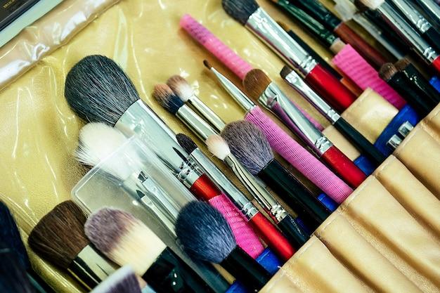 Много кистей для макияжа на столе в салоне красоты