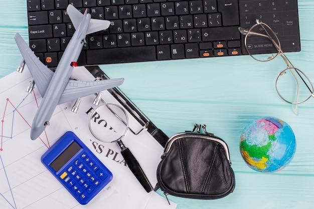 キーボード付きの青いテーブルにたくさんの厄介なもの。おもちゃの飛行機地球儀財布メガネ。飛行計画の概念。