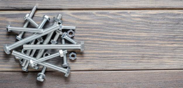 金属のボルトとナットがたくさん。固定用ツール。木製の背景。コピースペース