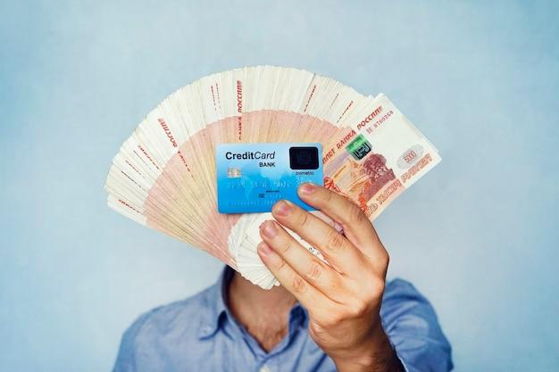 Много денег и кредитной карты в руке молодого бизнесмена на синем фоне. пачка банкнот российских рублей номиналом 5000 рублей. успешный бизнесмен