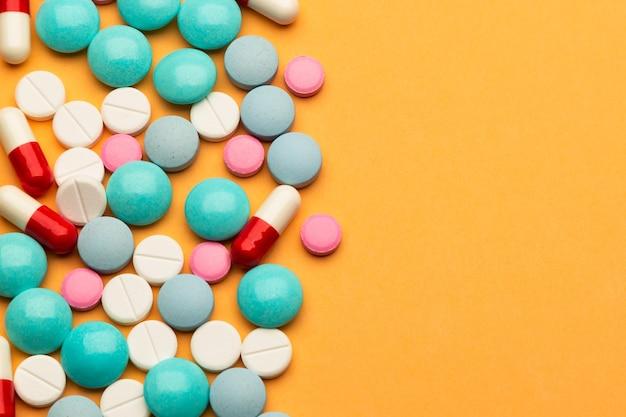 약물 중독의 개념으로 주황색 배경에 여러 가지 빛깔의 알약과 캡슐