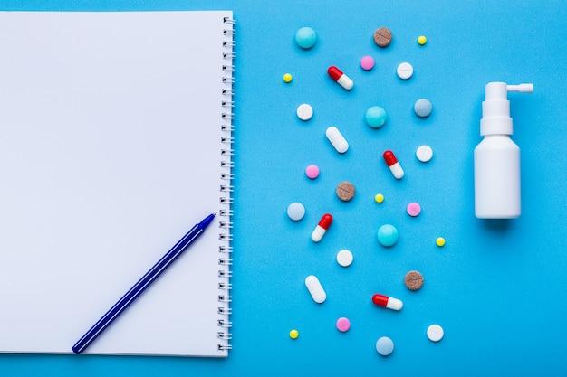 治療の概念をテキスト用の空きスペースと青い背景に色とりどりの丸薬がたくさん