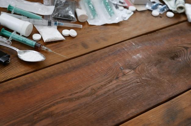 Множество наркотических веществ и приспособлений для приготовления лекарств лежат на старом деревянном столе