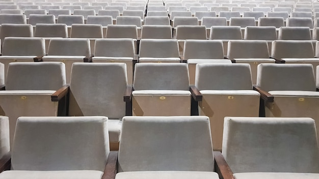 Много старых бежевых стульев с обивкой без людей в зале для спектаклей и фильмов. фон из множества стульев на трибунах концертного зала или театра.