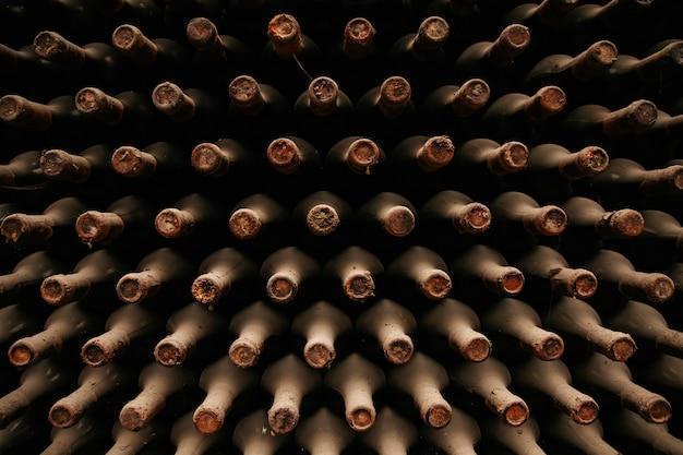 セラーの木製ラックに積み上げられた、ほこりの多いワインボトルで覆われた古いワインボトルがたくさん