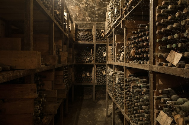 Много старых винных бутылок в сети в винном погребе на полках