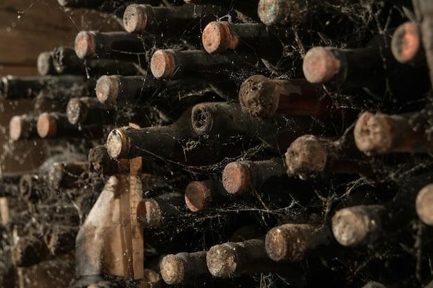 ワインセラーのウェブにある古いワインボトルがたくさん